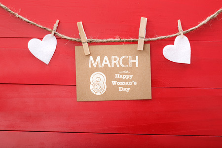 8 march: Womans day message with felt hearts hanging with clothespins over red wooden board