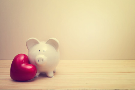 Piggy bank with red heart on a wooden table Reklamní fotografie - 36867429