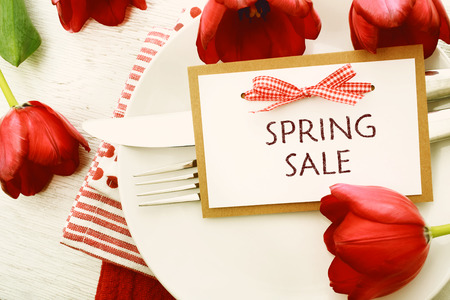 spring message: Dinner table setting with Spring Sale message card and red tulips