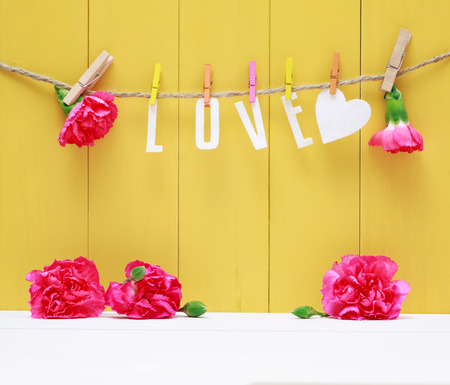 Hanging Love letters with pink carnation flowers over yellow wooden wall Imagens