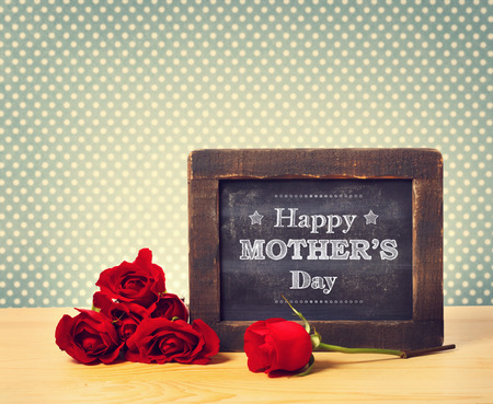 Happy Mothers Day message written on little chalkboard with roses