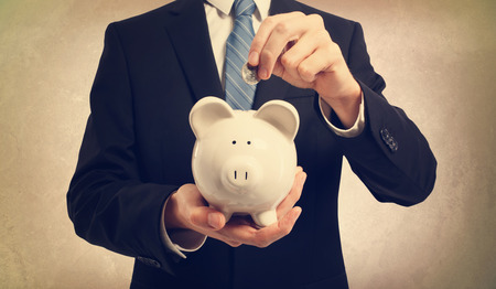 Young businessman depositing money in piggy bank Stock Photo