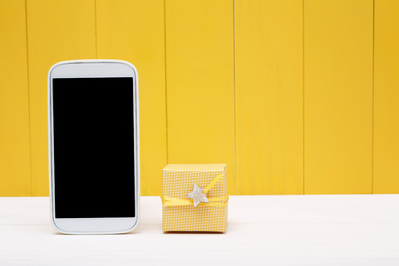 fathers day: Cellphone and small gift box over yellow wooden wall