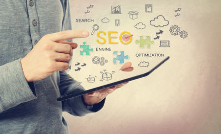 Young man pointing at SEO concept over a tablet computer photo