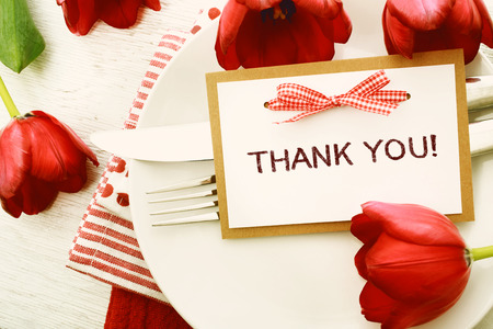 appreciation: Dinner table setting with Thank You message card and red tulips Stock Photo