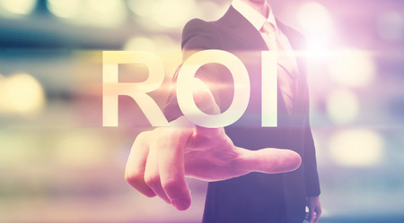 Businessman pointing at ROI (return on investment) on blurred city background photo
