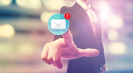 email: Businessman pointing at an email icon on blurred city background Stock Photo