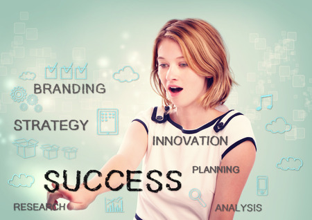 Young woman pointing at success concept on light blue background photo