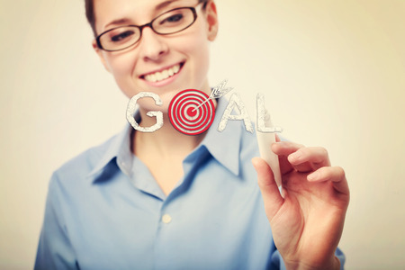 Smiling Young Businesswoman Writing GOAL Text on a Glass, Emphasizing Arrow on its Target