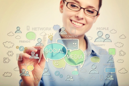 Young business woman with eyeglasses drawing social media concepts Stock Photo