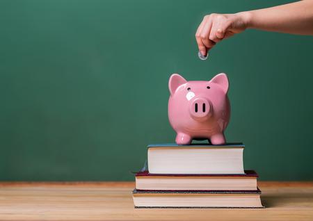 ahorros: Persona de depositar el dinero en una hucha rosa en la parte superior de los libros con la pizarra en el fondo concepto de imagen de los costos de la educación como Foto de archivo