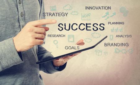 태블릿 컴퓨터를 통해 성공의 개념을 가리키는 젊은 남자