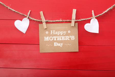 Moeders dag bericht met vilten hartjes opknoping met wasknijpers over rode houten plank Stockfoto
