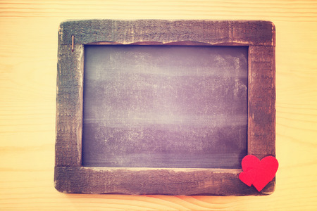 Empty Small Wooden Chalkboard with Red Hearts at the Corner on a Wooden Background