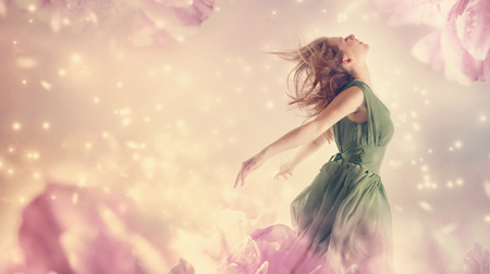 Beautiful woman in a green dress in a pink peony flower fantasy