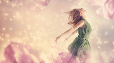 Mooie vrouw in een groene jurk in een roze pioen bloem fantasy Stockfoto