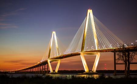 cooper: Arthur Ravenel Jr Bridge Illuminated in Evening over Cooper River Connecting Charleston and Mount Pleasant in South Carolina Stock Photo