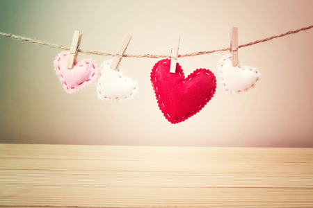 Four Small White, Pink and Red Hearts with Stitches Hanging on a String with Clothespin above the Wooden Table on Light Brown Background photo