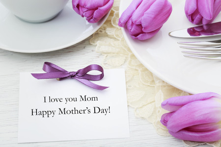 Mothers day card with table setting with purple tulips Stock Photo