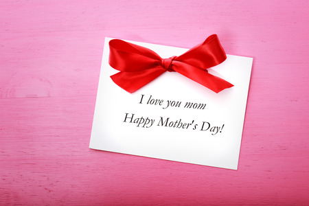 Mothers day message card with red ribbon on pink wooden board Stock Photo