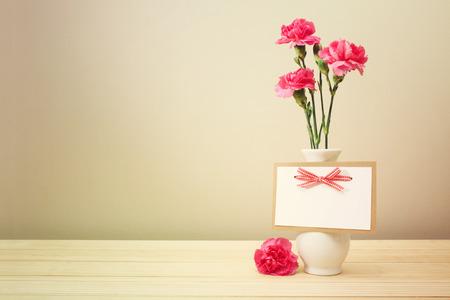 Jolie Rose Carnation fleurs sur blanc Vase avec Carte de voeux vierge sur table en bois avec le fond brun clair mur Banque d'images - 38197716
