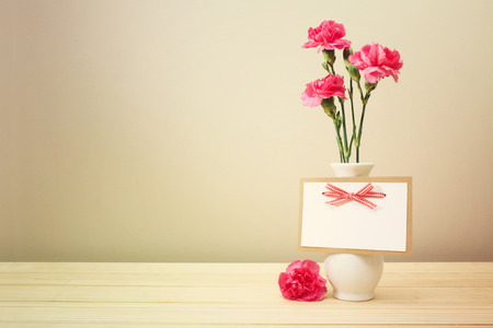 Pretty Pink Carnation Flowers on White Vase with Blank Greeting Card on Wooden Table with Light Brown Wall Background