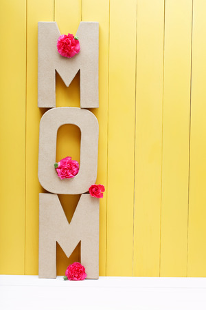 MOM text letters with pink carnations on yellow wooden background Stock Photo
