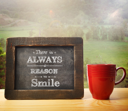 nature: There is always a reason to smile text on a little chalkboard with countryside and coffee relaxation theme Stock Photo