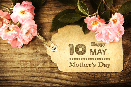 10th: May 10th Mothers Day card with small roses on wood background Stock Photo
