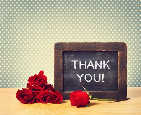agradecimiento: Gracias mensaje escrito en pequeña pizarra con rosas rojas Foto de archivo