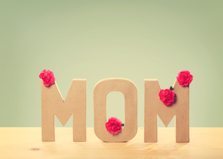 mothers day: 3D MOM Text with Fresh Carnation Flowers Standing on the Wooden Table with Light Green Background