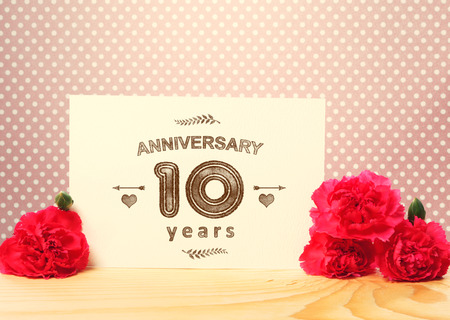 10 years anniversary: 10 years anniversary card with pink carnation flowers Stock Photo
