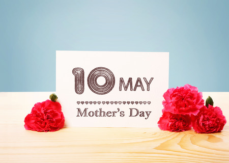 agradecimiento: Madres de Mayo Tarjeta 10 con Flores del clavel en la cima de una tabla de madera Foto de archivo