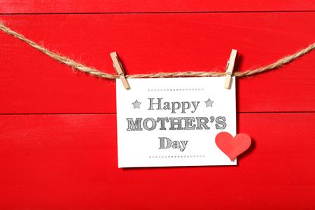 agradecimiento: Madres tarjeta de mensaje del d�a con un peque�o coraz�n rojo que cuelga con ganchos de ropa Foto de archivo