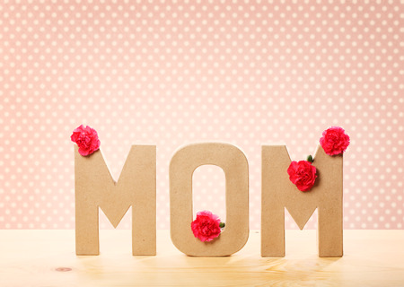 mom: 3D MOM Text with Fresh Carnation Flowers Standing on the Wooden Table with Pink Polka Dots Background Stock Photo