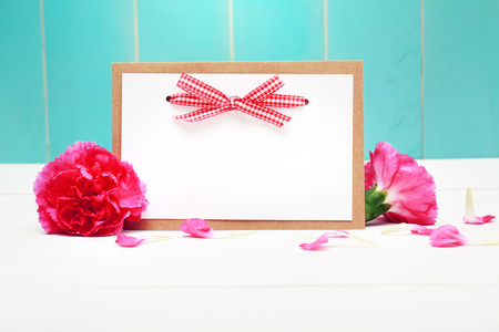 Card with carnation flowers on teal colored wooden wall Zdjęcie Seryjne