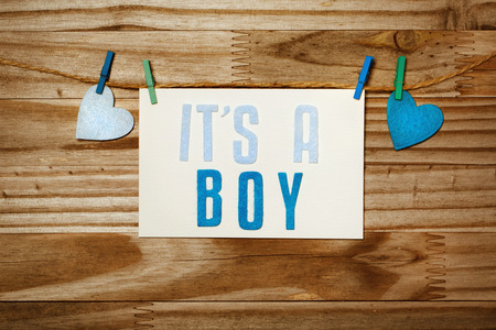 it's: ITS A BOY card and felt hearts hanging with clothespins Stock Photo