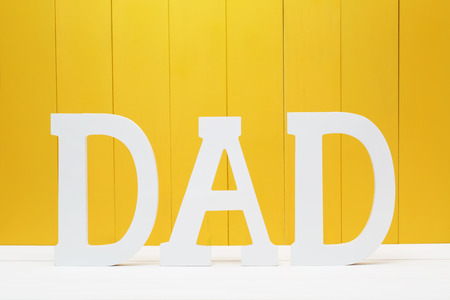 DAD text letters on yellow wooden wall background Stock Photo