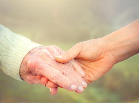 elder: Elderly woman holding hands with young caretaker