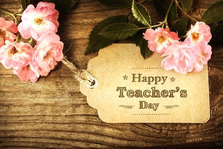 소박한 나무 테이블에 작은 핑크 장미와 행복 교사의 날 메시지 스톡 콘텐츠