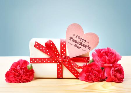 작은 선물 상자와 핑크색 카네이션이있는 행복한 선생님의 날 메시지 스톡 콘텐츠
