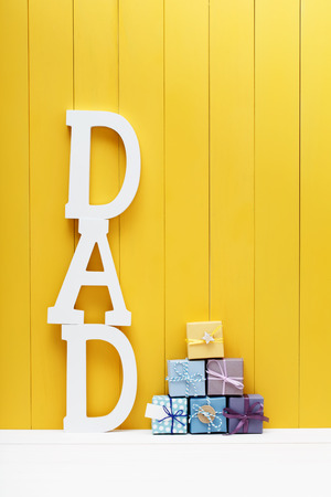 黄色の木製の背景上の小さなギフト箱とお父さんテキストを大文字 写真素材