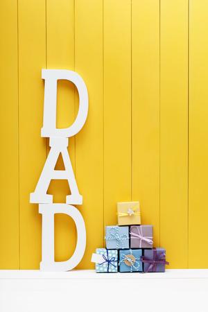 Letras de texto papá con pequeñas cajas de regalo sobre fondo amarillo de madera Foto de archivo - 39344687