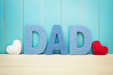 wood craft: DAD text letters with white and red hearts over blue wooden background