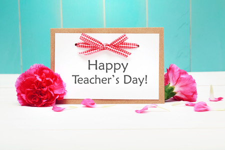 Happy Teachers Day card with pink carnations over teal wooden wall Stock Photo