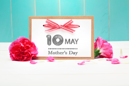 10th: May 10th Mothers Day card with pink carnations over teal wooden background