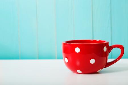 Red polka dot coffee mug on pastel blue background Foto de archivo