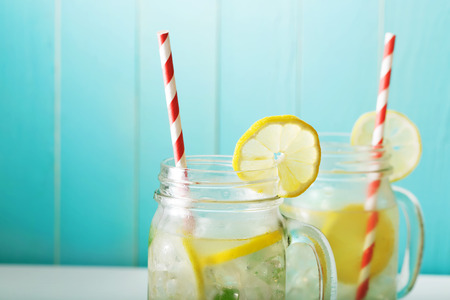 Homemade lemonade in mason jars with big red striped straws