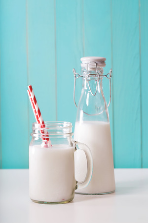 Old fashion milk jar and mason jar with big red paper striped straws on pastel blue background