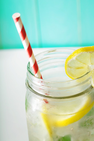 cold water: Homemade lemonade in a mason jar with big red striped straw